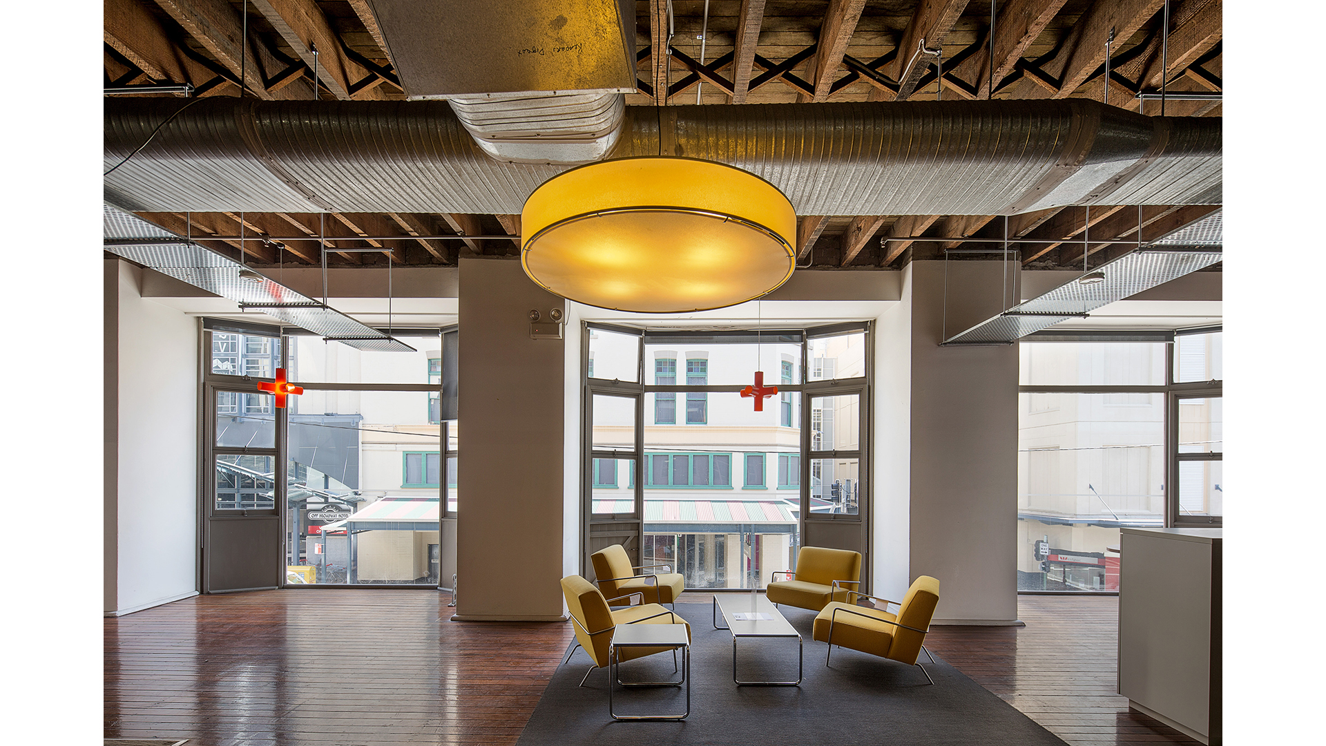 a modern office space with a big yellow lamp and chairs